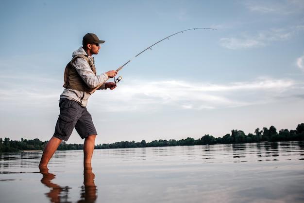 Aktiver mann steht im flachen und fischen. er hält die fliegenrute in händen. der mensch dreht sich um die rolle, um den löffel kürzer zu machen und fische zu fangen.