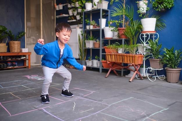 Aktiver netter lächelnder asiatischer kleinkindjunge, der das spaßspringen, hopse zu hause spielend hat