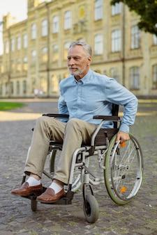 Aktiver reifer, sich erholender mann im rollstuhl, der weglächelt, während er zeit allein im park in der nähe verbringt