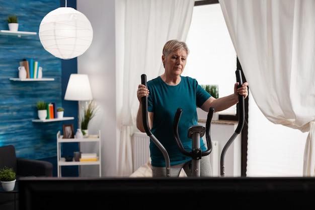 Aktiver ruhestand ältere frau, die beinmuskel mit fahrradfahrradmaschine arbeitet