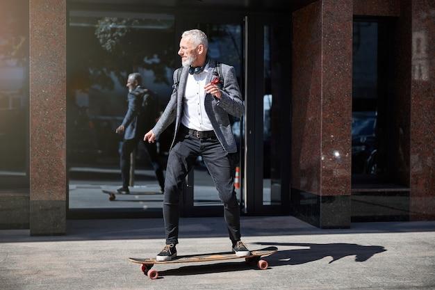 Aktiver senior, der beim fahren eines longboards auf der straße konzentriert aussieht
