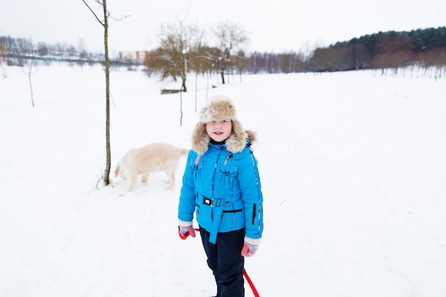 Aktiver spaß des winters - mädchen mit ihrem großen hund, der spaß im winterschneepark hat