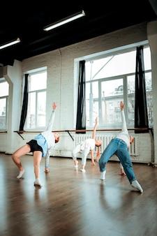 Aktiver tanz. die rothaarige tanzlehrerin trägt blue jeans und ihre schüler sehen beim tanzen flexibel aus Premium Fotos
