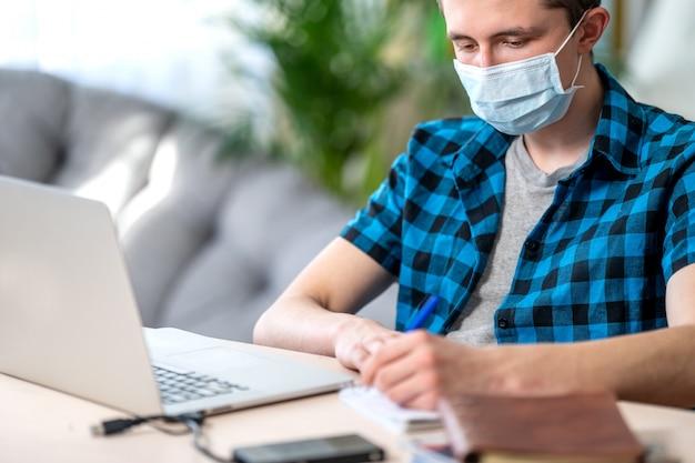 Aktiver teenager in maske mit laptop während der coronavirus-quarantäne