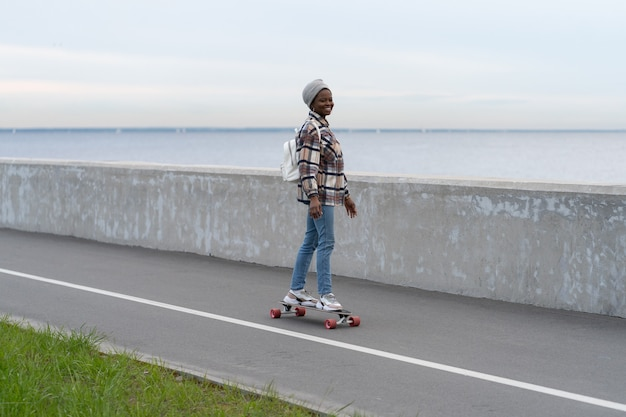 Aktiver urbaner lebensstil afrikanisches mädchen, das longboard an der küstenstraße reitet, lächelnde frau auf skateboard Premium Fotos