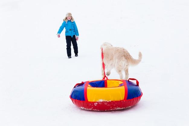 Aktiver winterspaß - mädchenfahrt vom schneehügel auf rohren und ein fröhlicher hund läuft daneben