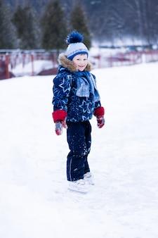 Aktiver winterurlaub - niedlicher kleiner junge, der auf eine eisbahn eisläuft