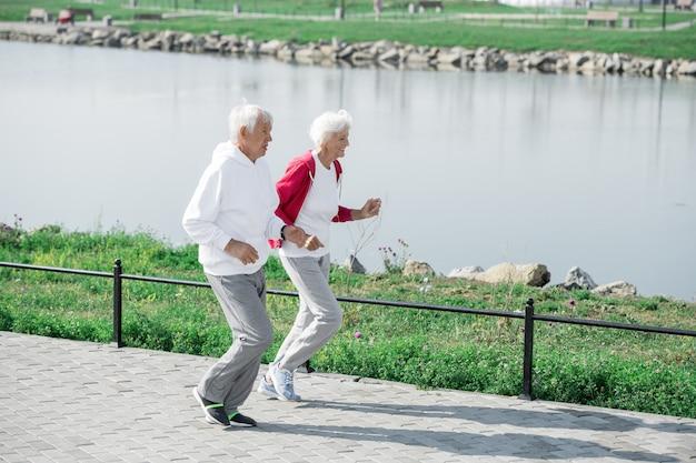 Aktives älteres paar, das durch teich läuft