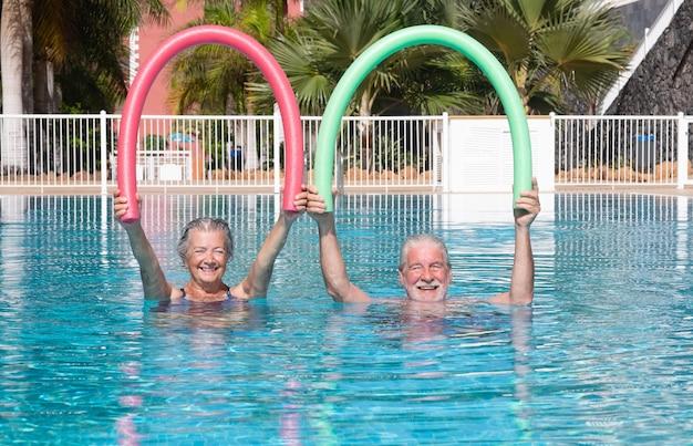 Aktives älteres paar, das im schwimmbad mit schwimmnudeln trainiert. glückliche rentner spielen im wasser des außenpools unter der sonne