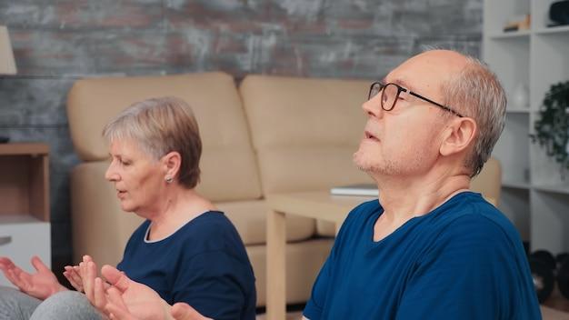 Aktives älteres paar, das zusammen im wohnzimmer meditiert. gesunder und aktiver lebensstil für ältere menschen zu hause, training und fitness für ältere menschen