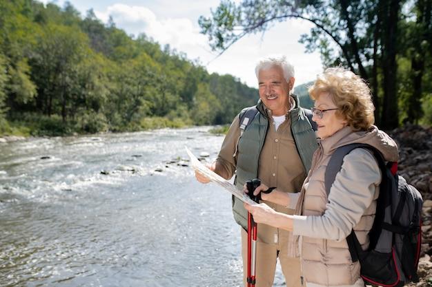 Aktives älteres paar mit rucksäcken, die karte betrachten, während an großem fluss in natürlicher umgebung während der reise stehen