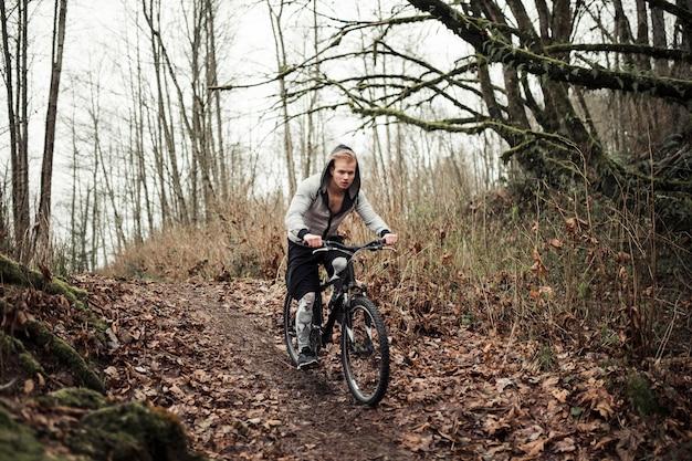 Aktives fahrrad des jungen mannes reitim wald