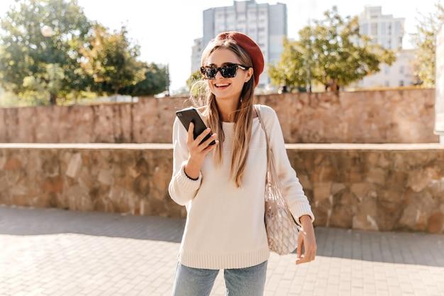 Aktives französisches mädchen in sonnenbrille und baskenmütze, die draußen kühlt. angenehme langhaarige frau mit telefon, das durch stadt geht.