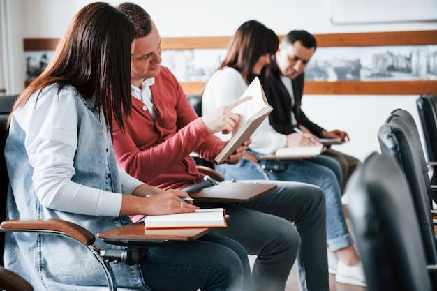 Aktives gespräch. gruppe von personen an der geschäftskonferenz im modernen klassenzimmer tagsüber
