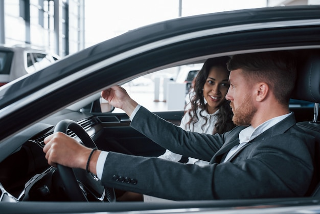 Aktives gespräch. schönes erfolgreiches paar, das neues auto im autosalon versucht