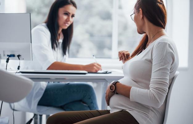 Aktives gespräch. schwangere haben drinnen rücksprache mit einem geburtshelfer.
