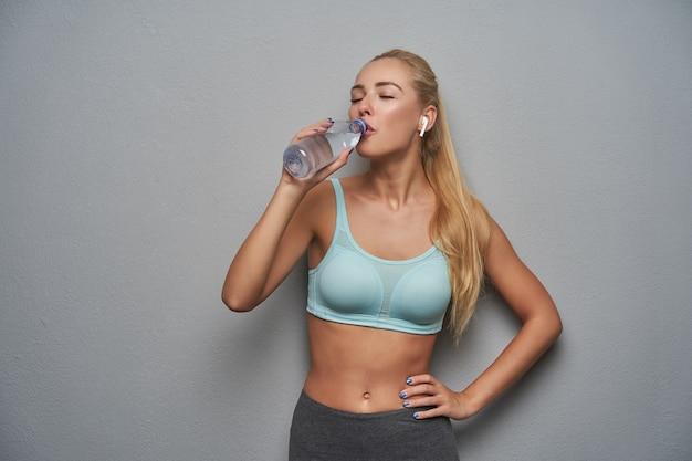 Aktives junges blondes modell mit pferdeschwanzfrisur, die minzsportoberteil und graue leggins trägt, während sie über grauem hintergrund aufwirft, quellwasser von flasche mit geschlossenen augen trinkend