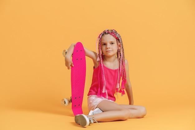 Aktives junges mädchen im rosa hemd und in den kurzen hosen, die auf skateboard über gelbem hintergrund sitzen