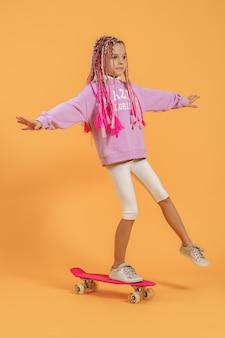 Aktives junges mädchen im rosa hemd und in den weißen shorts, die auf skateboard stehen