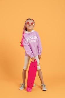 Aktives junges mädchen im rosa hemd und in den weißen shorts, die skateboard über gelbem hintergrund halten