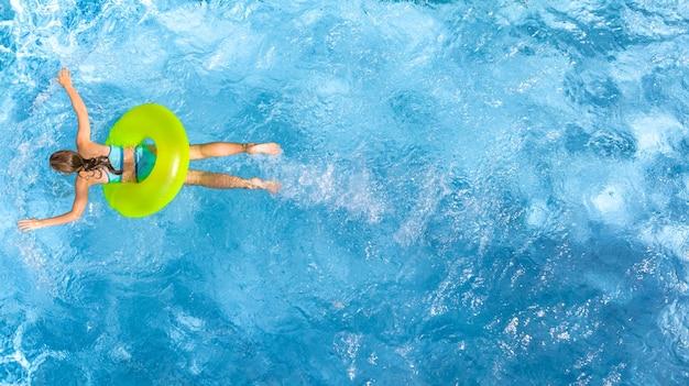 Aktives junges mädchen in der luftansicht des schwimmbades von oben, kind entspannt sich und schwimmt auf aufblasbarem ringkrapfen und hat spaß im wasser, tropischer ferienort