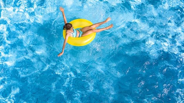 Aktives junges mädchen in der luftaufnahme des schwimmbades von oben, kind entspannt sich und schwimmt auf aufblasbarem ringkrapfen und hat spaß im wasser im familienurlaub, tropischer ferienort