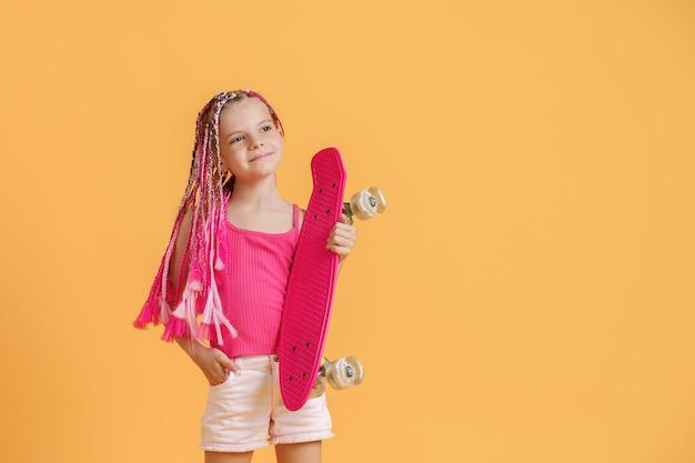 Aktives junges mädchen mit dreadlocks im rosa hemd und in den kurzen hosen mit pennyboard über gelbem hintergrund