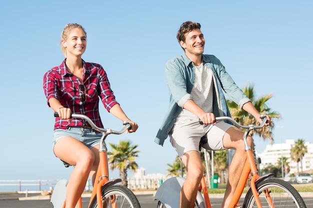 Aktives junges paar, das während der sommerferien fahrrad fährt