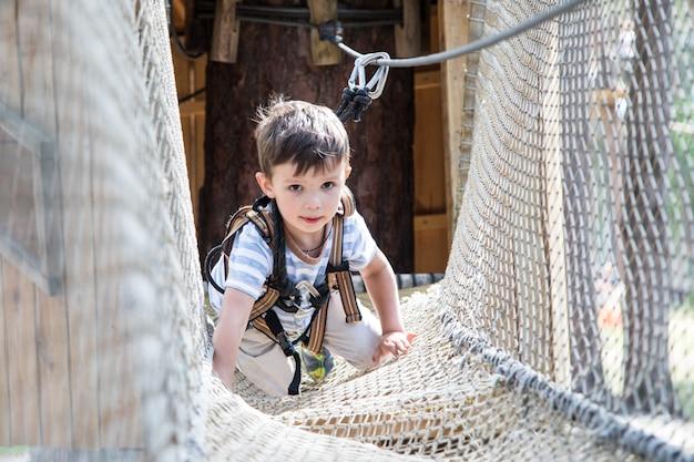 Aktives kleines kind, das auf kletternetz spielt. kinder spielen und klettern draußen am sonnigen sommertag.