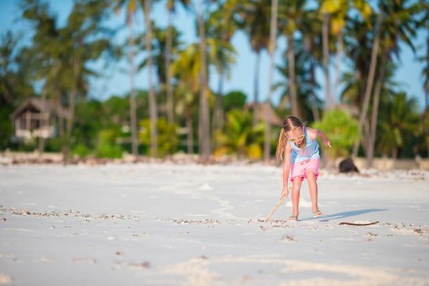 Aktives kleines mädchen auf dem weißen strand, der spaß hat. nahaufnahmekinderhintergrund das meer