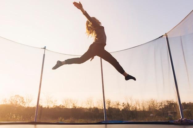 Aktives kleines mädchen, das über die trampoline gegen den himmel springt