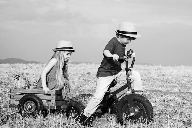 Aktives kleinkindkind, das draußen spielt und rad fährt. zwei kinder, die spaß im feld gegen blauen himmel haben