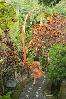 Aktives mädchen freut sich beim abstieg zu ihrem bungalow und genießt ihren urlaub auf bali