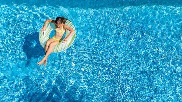 Aktives mädchen in der luftansicht des schwimmbades von oben, kind schwimmt auf aufblasbarem ringkrapfen, kind hat spaß im blauen wasser auf familienferienort