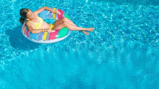 Aktives mädchen in der luftansicht des schwimmbades von oben, kind schwimmt auf aufblasbarem ringkrapfen, kind hat spaß im blauen wasser