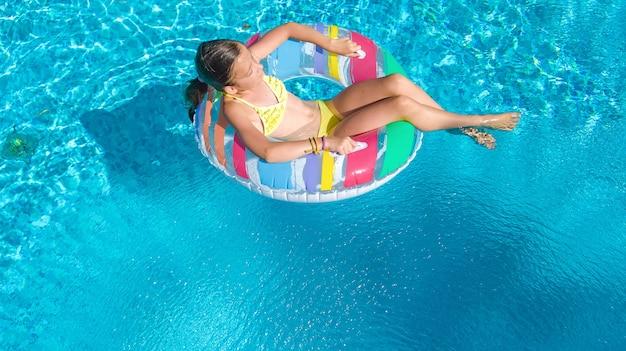 Aktives mädchen in der luftaufnahme des schwimmbades, kind schwimmt auf aufblasbarem ring