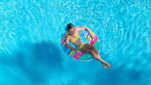 Aktives mädchen in der luftaufnahme des schwimmbades von oben, kind schwimmt auf aufblasbarem ringkrapfen, kind hat spaß im blauen wasser auf familienferienort