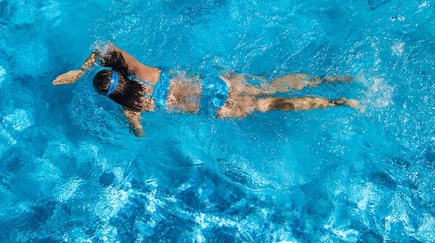 Aktives mädchen in der luftdrohnen-drohnenansicht des schwimmbades von oben, junge frau schwimmt im blauen wasser, tropischer urlaub, urlaub auf resortkonzept
