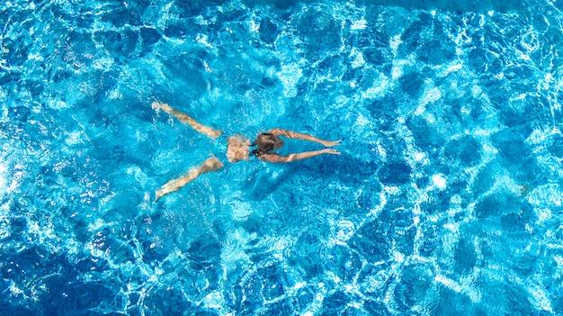 Aktives mädchen in der swimmingpoolluftbrummenansicht von oben, junge frau schwimmt im blauen wasser