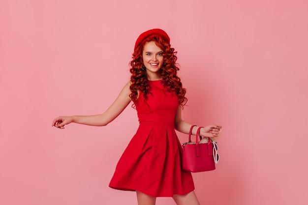 Aktives mädchen in stilvollem kleid und baskenmütze, die auf rosa raum aufwirft. rothaarige frau hält tasche und tanzt.
