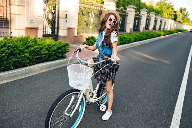 Aktives mädchen mit langen lockigen haaren im hut, der ein fahrrad auf straße fährt. sie trägt einen langen rock, ein wams und eine blaue sonnenbrille. sie hat spaß an der kamera.