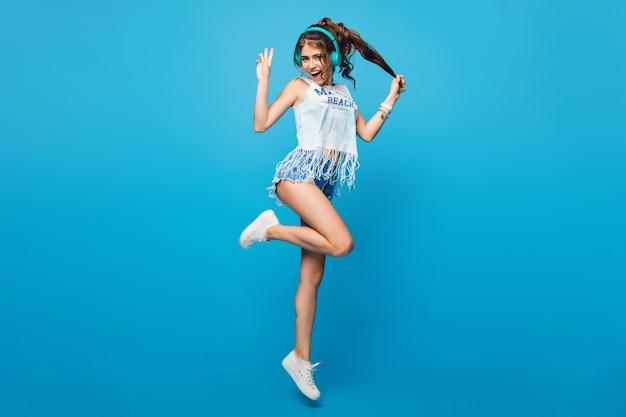 Aktives mädchen mit langen lockigen haaren im schwanz im sprung auf blauem hintergrund im studio. sie trägt ein weißes t-shirt und shorts. sie hört musik mit blauen kopfhörern.