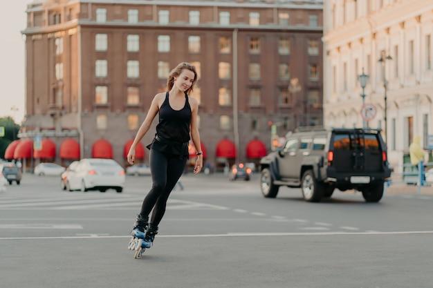 Aktives mädchen rollerblading auf grauem asphalt posiert auf rollen, die in aktiver kleidung gekleidet sind, führt schnell zu einem gesunden lebensstil, der sein lieblingshobby genießt. sport erholung rollschuhlaufen sommerzeitkonzept