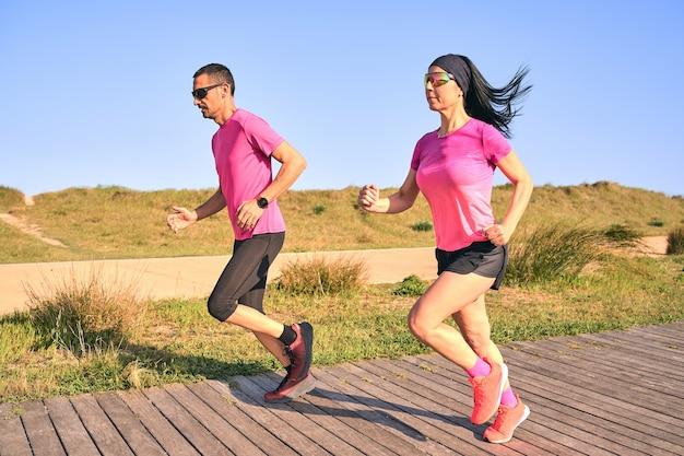 Aktives paar läuft an einem warmen sommertag. trägt rosa hemden und kurze hosen. beide tragen eine sonnenbrille. holzweg, umgeben von gras.