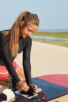 Aktives professionelles surfmädchen, gekleidet in badebekleidung, hat pferdeschwanz, repariert die leine und posiert an der küste