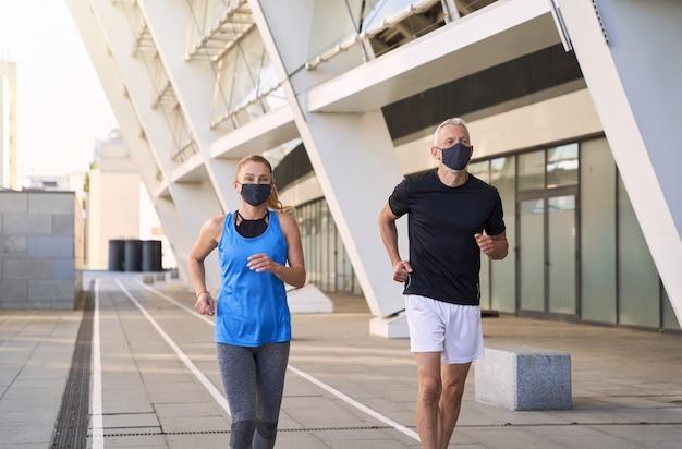 Aktives reifes paar mit schützenden gesichtsmasken, die zusammen in der städtischen umgebung joggen