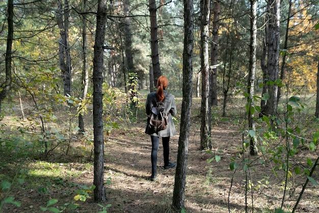 Aktives schönes rothaariges mädchen, das in den wald geht. frisches holz im freien, gesundes lifestyle-konzept des wellness. freie frau, die saubere luft im naturwald atmet