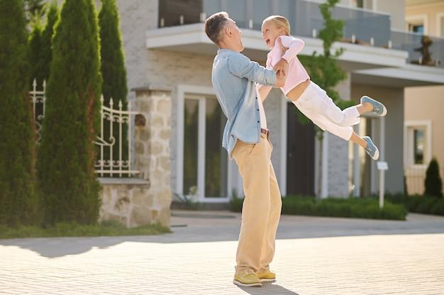 Aktives spiel. fröhlicher, energischer mann in freizeitkleidung, der an einem sonnigen tag die begeisterte kleine tochter hoch in seinen armen auf der straße hebt