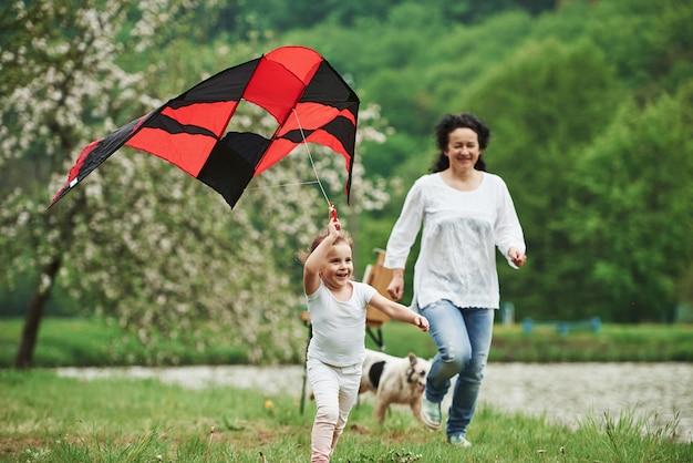 Aktives spiel. positives weibliches kind und großmutter, die mit rotem und schwarzem drachen in den händen draußen laufen