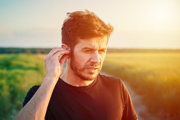Aktives tausendjähriges mannporträt im freien bei sonnenuntergang